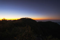 A group of people stands on a mountains at the sunrise. Silhouette A group of people stands on a mountains at the sunrise  On the top Doi Luang Chiang Dao Stock Photos