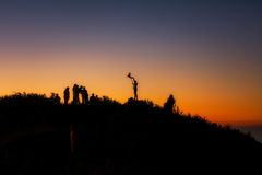 A group of people stands on a mountains at the sunrise. Silhouette A group of people stands on a mountains at the sunrise  On the top Doi Luang Chiang Dao Royalty Free Stock Image