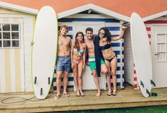 Group of people in swimsuit having fun outdoors. Group of young people in swimsuit with surfboards having fun in a summer day over a beach striped huts Stock Photo
