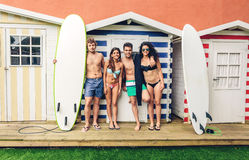 Group of people in swimsuit having fun outdoors. Group of young people in swimsuit with surfboards having fun in a summer day over a beach striped huts Royalty Free Stock Photo