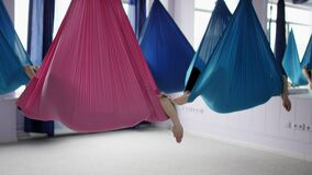 Group of people swings in an airy hammocks. Female bodies are folded inside gym during training models relax and enjoy