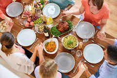 Group of people at table praying before meal. Breakfast, family and religious concept - group of people with food sitting at table and praying before meal stock images