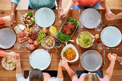 Group of people at table praying before meal. Breakfast, family and religious concept - group of people with food sitting at table and praying before meal Stock Photo