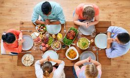 Group of people at table praying before meal Stock Image