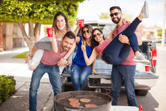 Group of people tailgating and grilling burgers. Group of young attractive friends tailgating, drinking beer and having some fun together next to a grill Royalty Free Stock Image