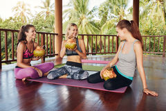Group of people taking a break from yoga workout. Three young women sitting together at yoga class and drinking green coconut juice. Group of people taking a Royalty Free Stock Photography