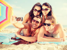 Group of people taking picture with smartphone. Summer, holidays, vacation, technology and happiness concept - group of smiling people in sunglasses taking royalty free stock photography