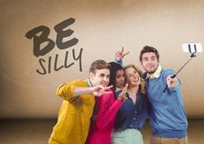 Group of people taking selfie in front of Be Silly text. Digital composite of Group of people taking selfie in front of Be Silly text Stock Photography