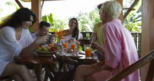 Group of people talking using cell smart phones sit together at table on terrace surfing internet outdoors, friends. Chatting online slow motion 60 stock footage