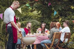 People grilling in garden. Group of people in their twenties and thirties in the garden enjoying their time together, eating and drinking, by a table stock photography