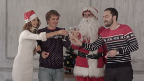Group of people toasting at a celebration of. Christmas and clinking their glasses together. They drink champagne and then blow favor horns. Professional shot stock video