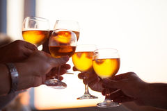 Group of people toasting with white wine. High key image of the hands of a group of people toasting with white wine at a celebration silhouetted against a bright Stock Photography