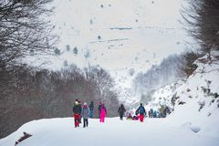 Group of people in a tour at a snowy mountain. Winter fun excursion stock photography