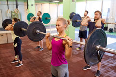 Group of people training with barbells in gym Stock Photography