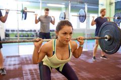 Group of people training with barbells in gym Stock Photos