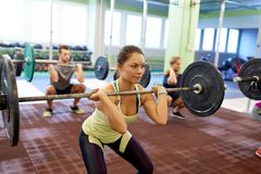 Group of people training with barbells in gym Stock Image