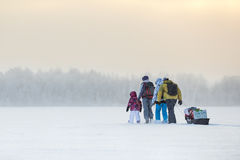 Group of people traveling over ice of frozen lake through snowing at winter time Royalty Free Stock Photography
