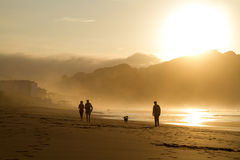 A group of people trek along the wet shore at dusk. Royalty Free Stock Images
