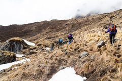 Group of people trekking a barren ascending hill with snow and dried grass Royalty Free Stock Photo