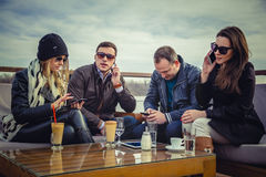 A group of people using cell phone. While sitting by the river Stock Photo