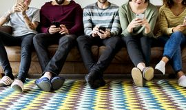 Group of people using mobile phone on couch Royalty Free Stock Image
