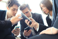 Group of people using smart phones sitting at the meeting, close up on hands. Royalty Free Stock Photos