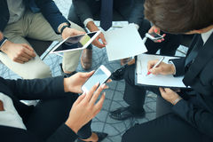 Group of people using smart phones sitting at the meeting, close up on hands. Royalty Free Stock Image