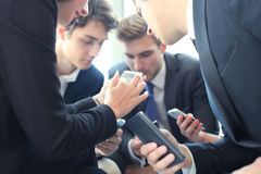 Group of people using smart phones sitting at the meeting, close up on hands. Stock Images