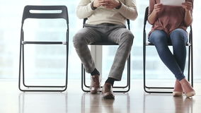 Group of people waiting for job interview. Group of three young candidates sitting on chairs in modern office, waiting and going one after another to job stock footage