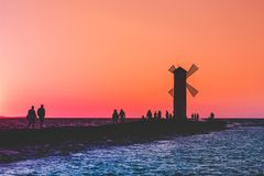 A group of people walk along the pier near the lighthouse on the sea at sunset.  royalty free stock photos