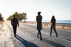 Group of people walk along the road at the seaside. Three young stock image