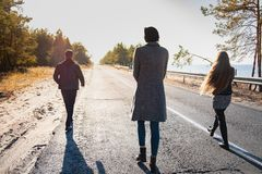 Group of people walk along the road at the seaside. Three young. Persons walking in beautiful nature scene in late summer or autumn royalty free stock photos