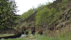 Group of people walking by the stream. Group of four adult people walking along small canalized stream in the hilly rural area stock footage