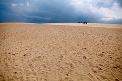 Group of people wandering through desert. Sand dunes and a storm on the horizon Royalty Free Stock Images