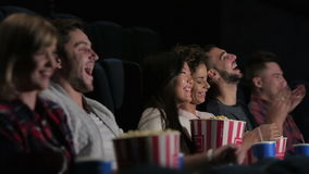 A group of people watching a movie showing emotion. Cinema, entertainment and people concept - happy friends watching movie in theater. Couple and other people stock video