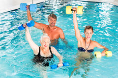 Group of people at water gymnastics or aquarobics. Group of people, mature man, young and senior women, at water gymnastics or aquarobics Royalty Free Stock Photos