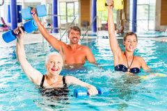 Group of people at water gymnastics or aquarobics. Group of people, mature man, young and senior women, at water gymnastics or aquarobics Stock Image
