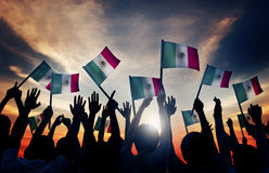 Group of People Waving Mexican Flags in Back Lit Stock Image