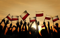 Group of People Waving Polish Flags in Back Lit Royalty Free Stock Photo