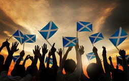 Group of People Waving Scottish Flags in Back Lit Royalty Free Stock Image