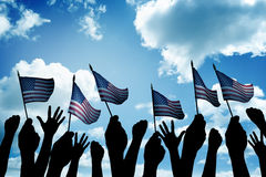 Group of people waving small USA flag. Facing blue sky Royalty Free Stock Images