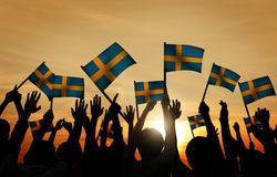 Group of People Waving Swedish Flags in Back Lit Royalty Free Stock Images