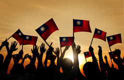 Group of People Waving Taiwanese Flags in Back Lit.  Stock Photo