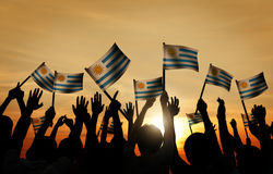 Group of People Waving Uruguayan Flags in Back Lit Stock Image