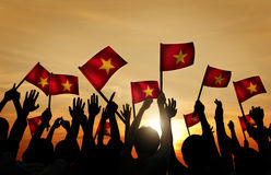 Group of People Waving Vietnamese Flags in Back Lit Stock Image