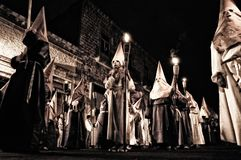 Group Of People In White Hood Holding Torch on Street stock image