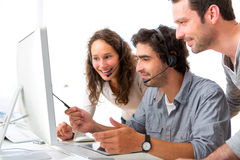 Group of people working around a computer Royalty Free Stock Photo