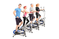 A group of people working on a cross trainer machine Stock Photo
