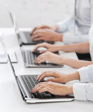 Group of people working with laptops in office. Business, school and education concept - group of people working with laptops in office royalty free stock photo