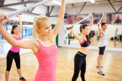 Group of people working out with barbells in gym. Fitness, sport, training, gym and lifestyle concept - group of smiling people working out with barbells in the Royalty Free Stock Photo